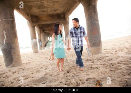 Couple Holding Hands, marche pieds nus sous une jetée