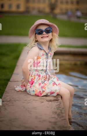 Fille assise avec ses pieds dans l'eau making a face Banque D'Images