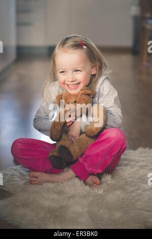 Fille assise sur le sol serrant son ours en peluche Banque D'Images