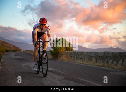 Homme randonnée à vélo au coucher du soleil, Corse, France
