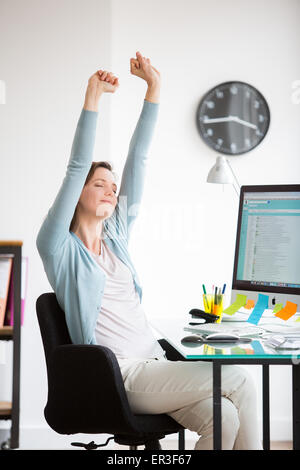 Office woman stretching arms au travail. Banque D'Images