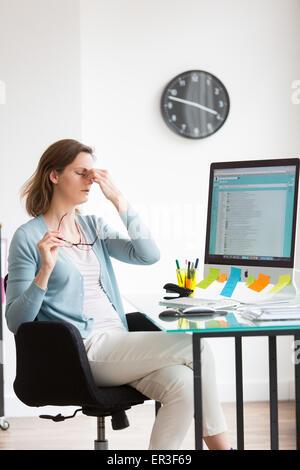 Femme au travail souffrant de maux de tête. Banque D'Images