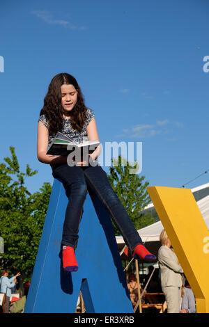 Hay Festival, Powys, Wales - Mai 2015 - Jeune fille lisant un livre assis sur le dessus de la FOIN géant signe sur Banque D'Images