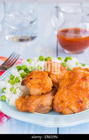 Haut de cuisses de poulet mariné et cuit dans une sauce vinaigrette russe, servi avec du riz et des pois Banque D'Images