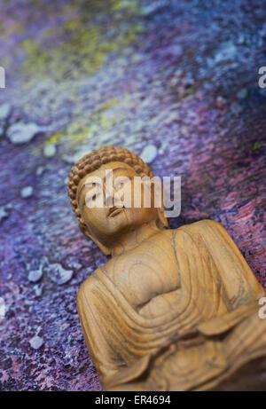 Bouddha en bois sur un fond peint cosmique Banque D'Images