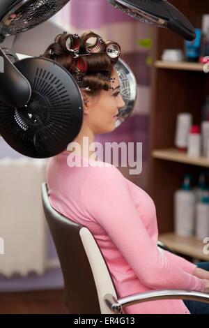 Jeune femme assise sous un sèche-cheveux avec rouleaux. Debica, Pologne Banque D'Images