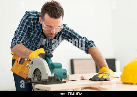 L'accent carpenter scier du bois. Pilzno, Pologne Banque D'Images