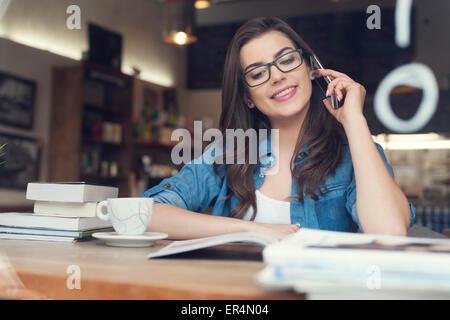 Souriante jeune femme parlant au téléphone dans le café. Cracovie, Pologne Banque D'Images