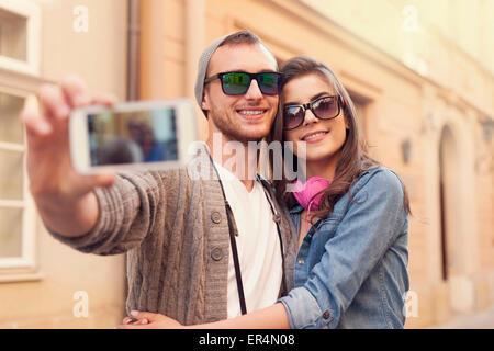Couple à la mode par selfies téléphone mobile. Cracovie, Pologne Banque D'Images