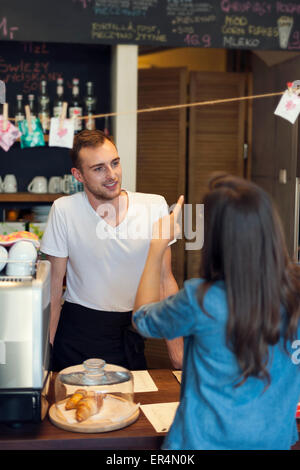 Smiling waiter reçoit l'ordre de jeune femme. Cracovie, Pologne Banque D'Images