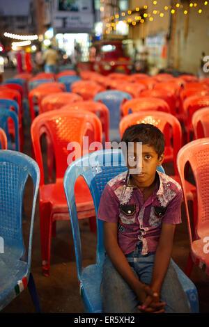 Garçon assis sur une chaise en face d'une scène, Mysore, Karnataka, Inde Banque D'Images