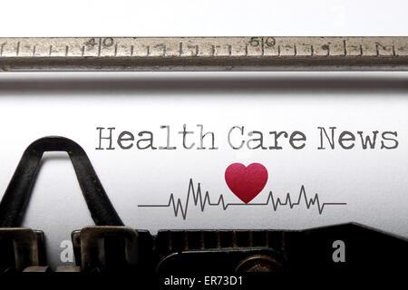 Soins de santé nouvelles imprimée sur une vieille machine à écrire avec des croquis d'impulsion du rythme cardiaque Banque D'Images