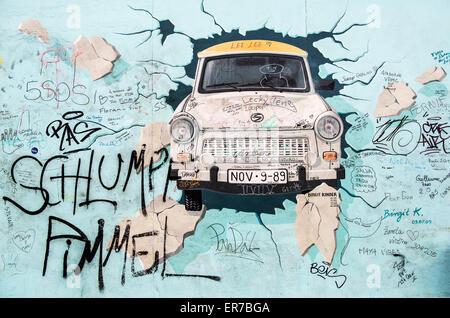 Illustrations sur le mur de Berlin à l'East Side Gallery représentant une voiture Trabant briser le béton. Banque D'Images