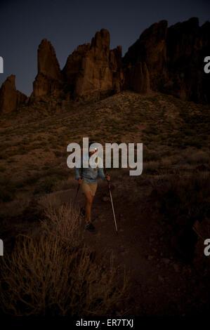 Randonnées femme de nuit par projecteur sur le sentier en boucle de trésor dans Lost Dutchman State Park près de Banque D'Images