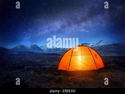 Une tente de camping brille sous un ciel plein d'étoiles. Camping en plein air d'aventure. Banque D'Images