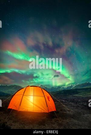 Une tente de camping glowing sous les aurores boréales. Camping de nuit scène. Banque D'Images