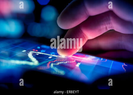 Une ville d'affaires à l'aide d'un appareil mobile pour vérifier les stocks et les données du marché. Close up shot.