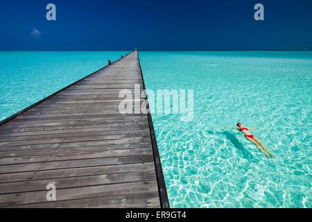 Young woman in red bikini piscine à côté de l'eau jetée dans azure des Maldives