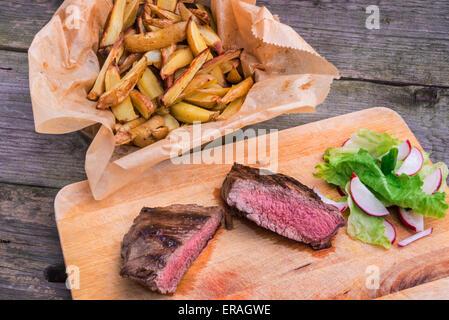 Rare moyen haut pavé de rumsteak grillé assaisonné de poivre vert et le thym, servi sur une planche en bois avec Banque D'Images
