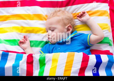 Enfant dormant dans un lit coloré. Petit bébé garçon endormi. Textiles enfants arc-en-ciel de couleur. Tout-petit Banque D'Images
