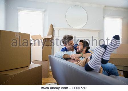 Couple homosexuel affectueux canapé parmi des cartons Banque D'Images
