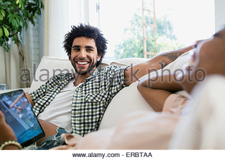 Couple Laughing with digital tablet in living room Banque D'Images