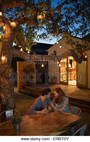 Affectionate couple drinking wine at table patio Banque D'Images