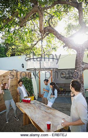 Cheering amis jouant Beer Pong sur patio ensoleillé Banque D'Images