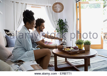Couple pouring coffee in living room Banque D'Images