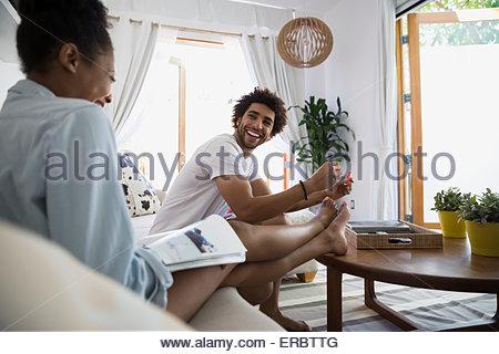 Man giving girlfriend pédicure dans la salle de séjour Banque D'Images