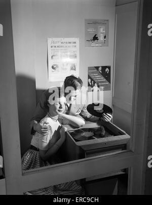 1950 COUPLE SITTING IN STORE STAND D'ÉCOUTE RECORD HOMME AVEC BRAS AUTOUR DE WOMAN HOLDING 78 TR/MIN Banque D'Images