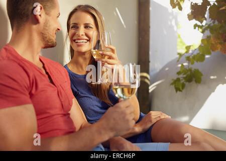 Beau coup de jeune couple buvant un verre de vin blanc sur une terrasse extérieure. Banque D'Images