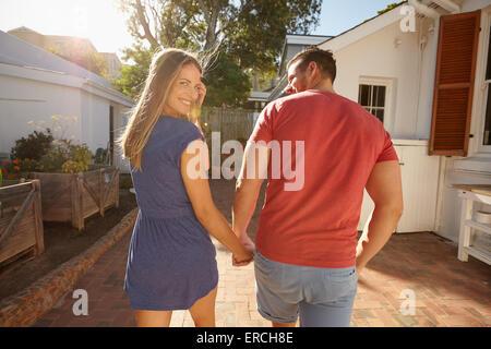 Jeune couple en train de marcher à leur chambre, la main dans la main par un beau jour d'été, avec femme retour Banque D'Images