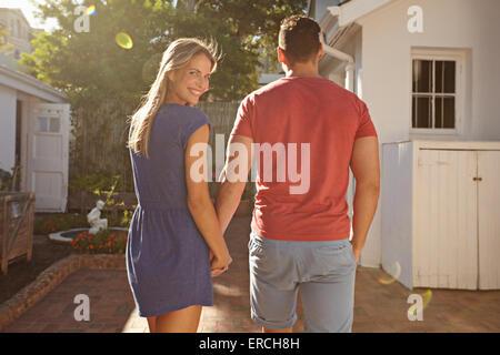 Young caucasian couple marche dans l'arrière-cour tenant la main dans la main par un beau jour d'été, avec femme Banque D'Images