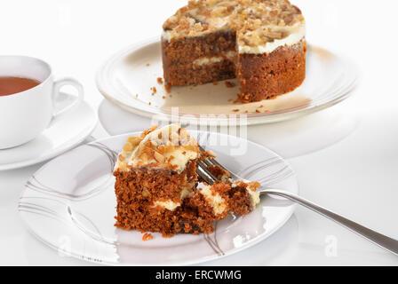 Gâteau aux carottes slice servi sur une assiette avec une fourchette sur une surface blanche. Tasse de thé. Selective focus