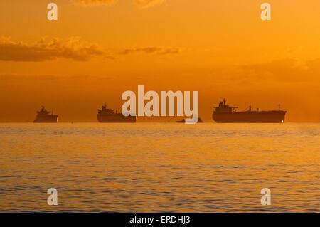 Navires en attente au mouillage dans le golfe du Mexique, au lever du soleil, avant d'entrer dans la baie de Galveston sur le chemin de Port de Houston, Texas, États-Unis