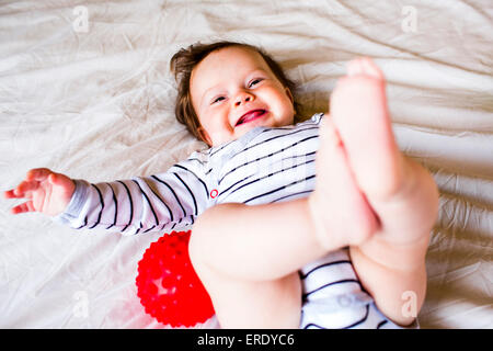Caucasian baby girl laughing on bed Banque D'Images