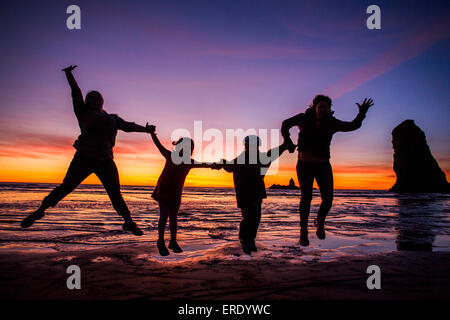 Silhouette of Caucasian family sauter de joie sur Cannon Beach, Oregon, United States Banque D'Images