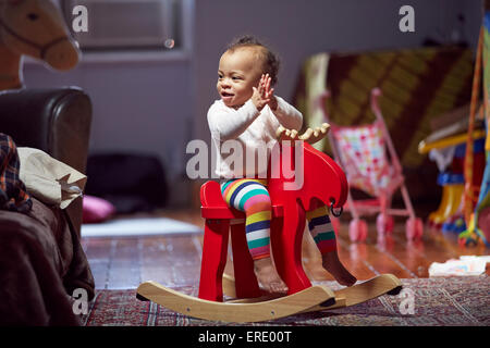 Mixed Race baby girl playing on Rocking Horse Banque D'Images