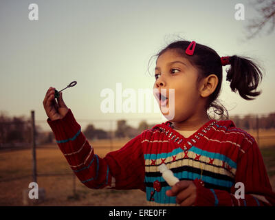 Mixed Race girl blowing bubbles in field Banque D'Images