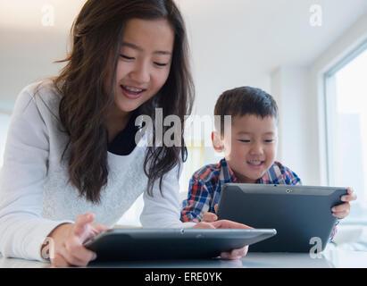 Frère et soeur de l'Asie à l'aide de tablettes numériques à table Banque D'Images