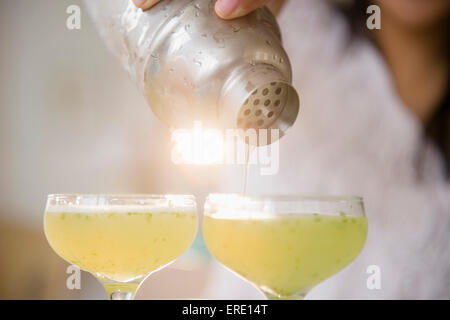 Pacific Islander woman pouring cocktail shaker