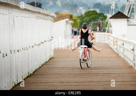Older Caucasian woman riding bicycle on wooden dock Banque D'Images