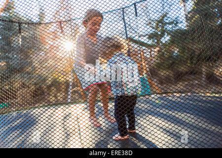 Frère et soeur de race blanche de sauter sur le trampoline Banque D'Images