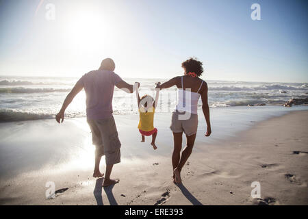 Mixed Race parents lifting daughter on beach Banque D'Images