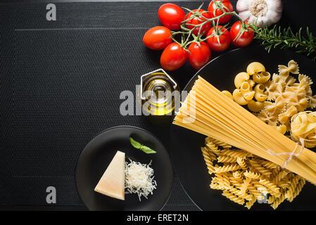 Collection de pâtes et d'ingrédients frais sur un fond noir l'analyse des frais généraux Banque D'Images