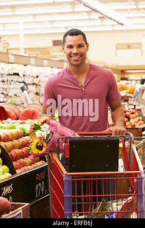 Man Pushing Trolley par Comptoir de fruits au supermarché Banque D'Images