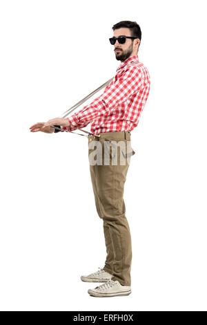 Hipster excentrique qui s'étend des bretelles à la recherche à distance. La longueur du corps complet isolé portrait Banque D'Images