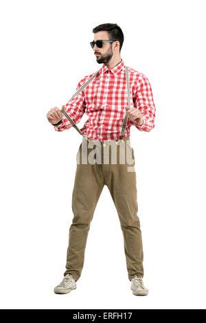 Jeune hipster barbu bretelles tirant à distance. La longueur du corps complet isolé portrait sur fond blanc. Banque D'Images