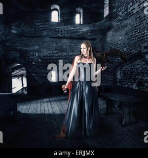 Belle jeune femme vampire aristocrate avec une tasse de sang se situe dans le vieux château Banque D'Images
